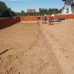 Wkopywanie siatki na krety podczas zakładania ogrodu Kraków